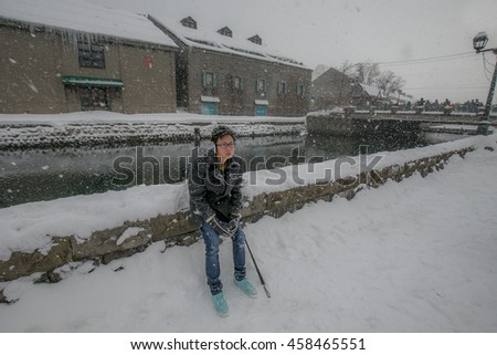 Asian men sitting alone in Otaru canal with heavy snow