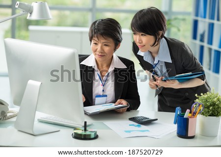 Asian middle aged businesswoman showing something on the monitor to her young colleague - stock photo