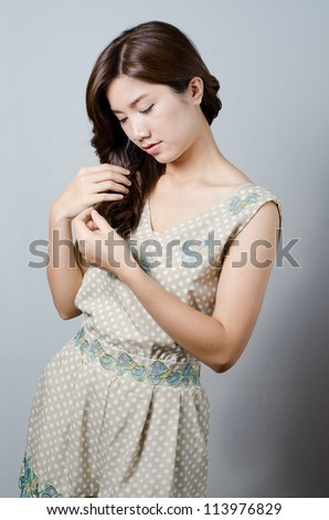 Asian model girl doing her hair - stock photo