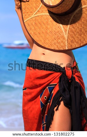 Asian model holding a hat  on the beach in Thailand - stock photo