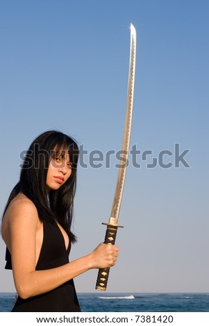 Asian model posing with a sword against blue sky - stock photo