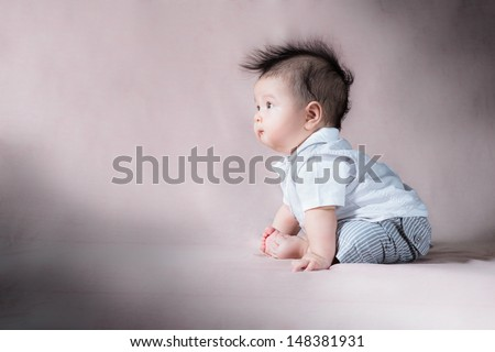 Asian 5 month old baby sitting up with wild mohawk hair making a funny face