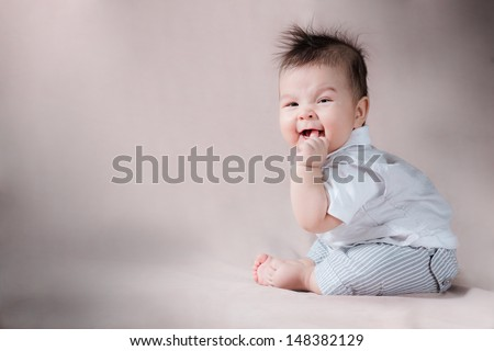 Asian 5 month old baby sitting up with wild scruffy hair and smiling while sucking thumb - stock photo