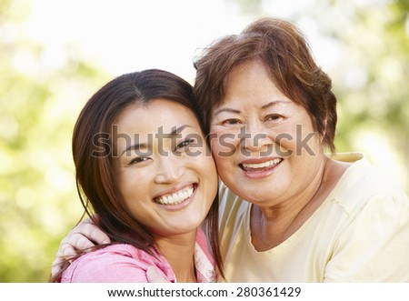 Asian mother and adult daughter head and shoulders outdoors - stock photo