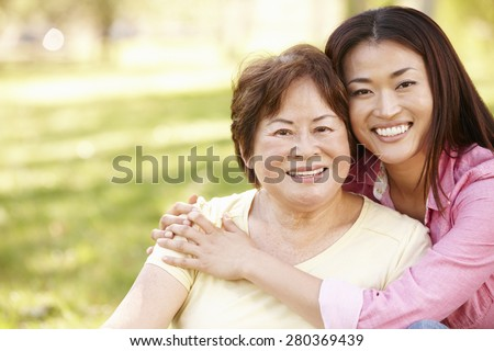 Asian mother and adult daughter portrait outdoors - stock photo