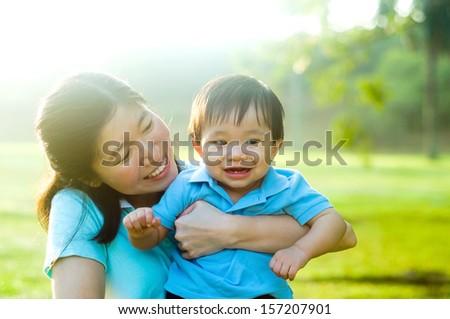 Asian mother and baby enjoying morning sunshine - stock photo