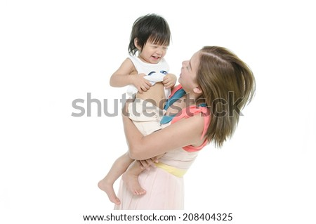 Asian mother and baby kissing, laughing and hugging - stock photo