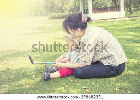 Asian mother and baby  taking selfie photography in the outdoor park  - stock photo