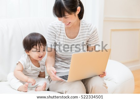 asian mother and baby using laptop computer