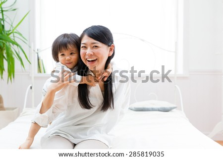 asian mother and child relaxing on the bed room - stock photo