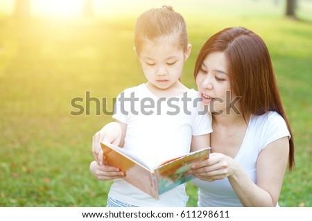 Asian mother and daughter are reading book and having fun in nature. Family outdoor fun, morning with sun flare.