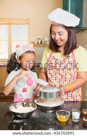 Asian mother and daughter enjoy making pancake, Asian mom teaching daughter to learn making pancake in real life kitchen at home