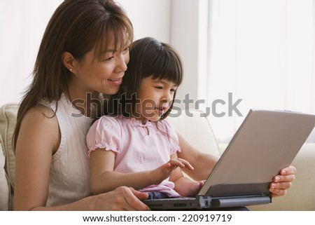 Asian mother and daughter looking at laptop - stock photo