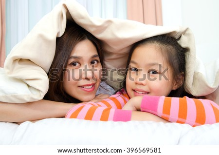 Asian mother and daughter lying on the bed - stock photo
