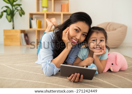 Asian mother and daughter lying on the floor with tablet computer - stock photo