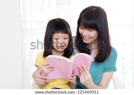Asian mother and daughter reading a book - stock photo