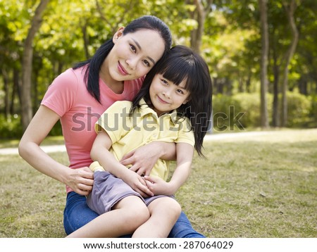 asian mother and daughter sitting on grass in a park. - stock photo