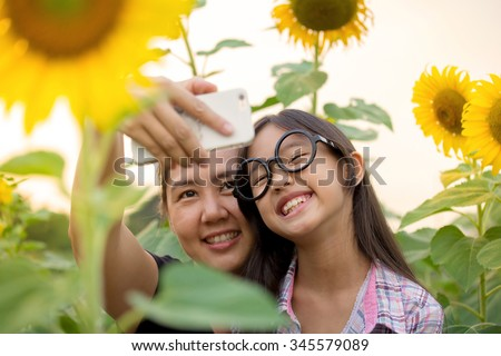 Asian mother and daughter taking selfie photograph together - stock photo