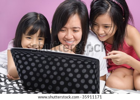 Asian mother and daughters playing with laptop in the bedroom