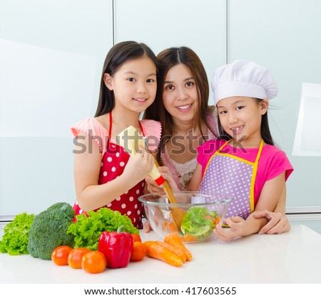 Asian mother and daughters preparing salad in the kitchen