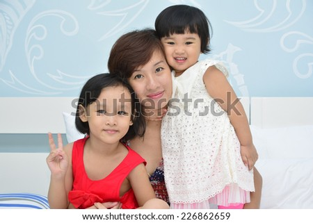 Asian mother and 2 daughters sit on the white bed - stock photo