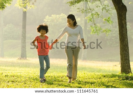asian mother and daugther  walking in the park - stock photo