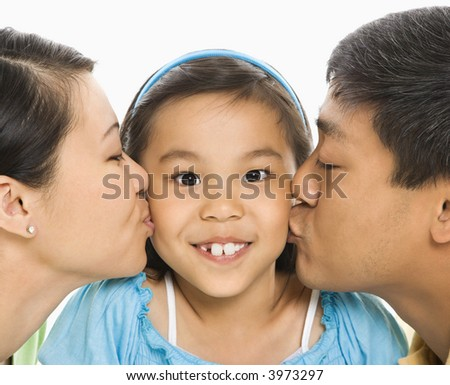 Asian mother and father kissing opposite cheeks of smiling daughter in front of white background.