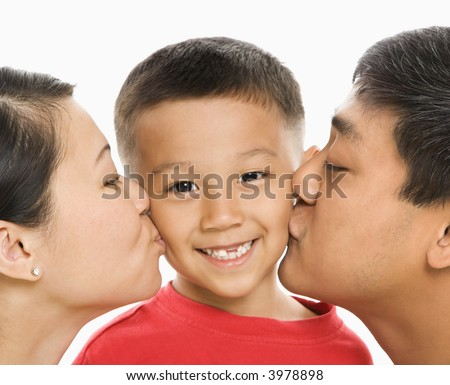 Asian mother and father kissing opposite cheeks of smiling son in front of white background. - stock photo