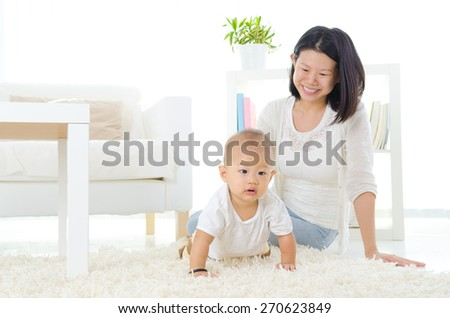 Asian mother and her crawling baby - stock photo