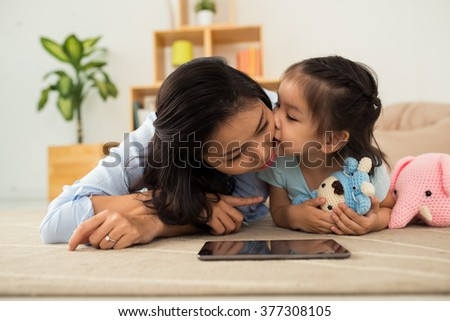 Asian mother and her little daughter playing on the floor - stock photo