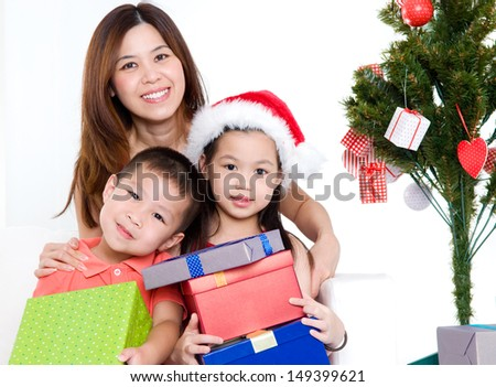 Asian mother and kids holding christmas gift looking at camera - stock photo