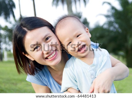 asian mother and son enjoying morning sunshine in the garden - stock photo