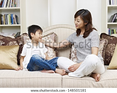 asian mother and son having a conversation on couch at home - stock photo