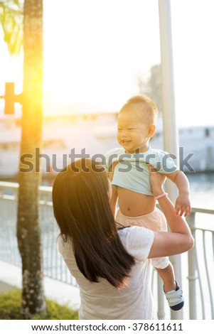 Asian mother and son having fun at outdoor in sunset during holidays. - stock photo