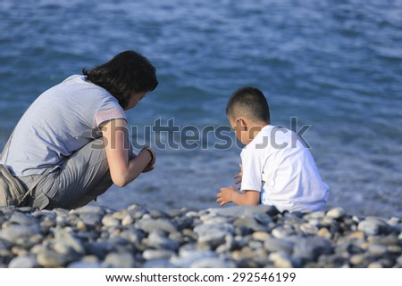 Asian mother and son playing at seaside,Taiwan - stock photo