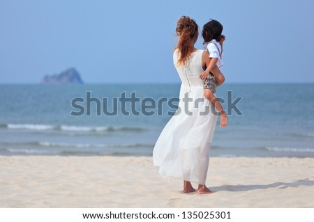Asian mother and son playing on tropical beach - stock photo