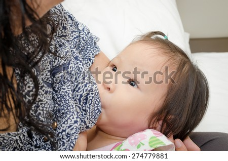Asian mother breast feeding her daughter - stock photo