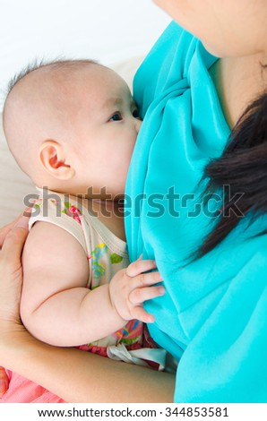 Asian mother breastfeeding her three months old baby - stock photo