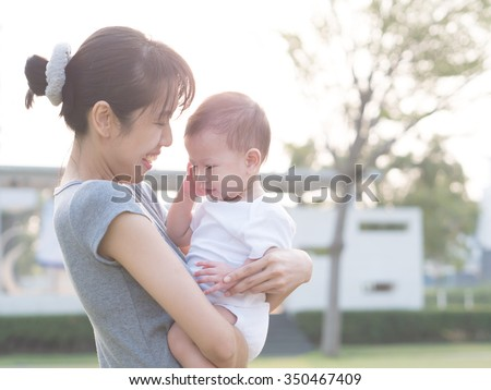 Asian mother carry baby outdoor.