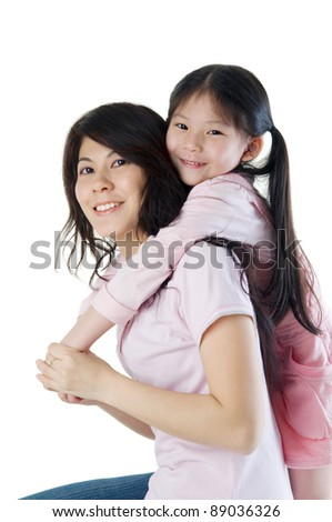 Asian mother giving piggyback ride to her daughter, isolated on white background - stock photo
