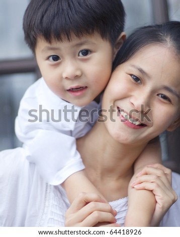 asian mother giving son piggyback ride