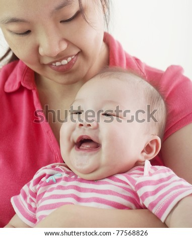 Asian mother holding her cheerful baby girl - stock photo