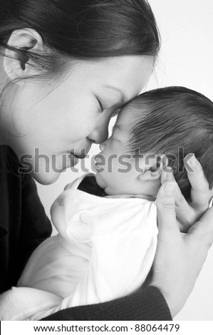 Asian mother holding her new born baby in sepia tone - stock photo