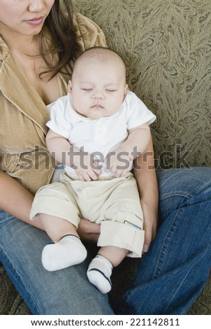 Asian mother holding sleeping baby - stock photo