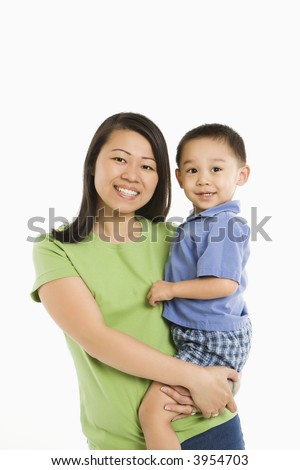 Asian mother holding son on hip smiling in front of white background. - stock photo