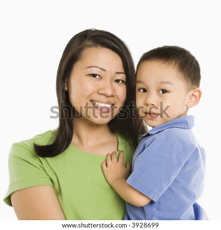 Asian mother holding son smiling in front of white background.
