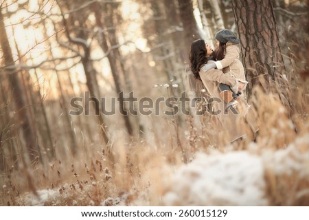 Asian mother holds on hands her little cute daughter in winter forest with tenderness  in the evening when the sun goes down - stock photo