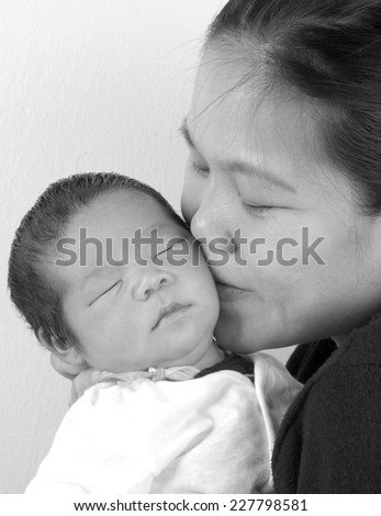 Asian mother kiss her new born baby in sepia tone - stock photo
