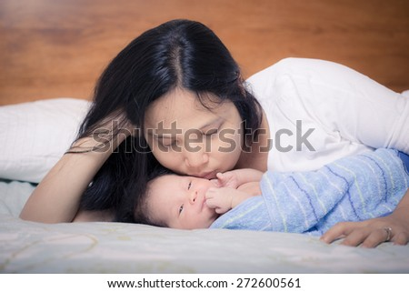 Asian mother lays on her bed in her bedroom with her freshly bathed mixed race 10 day old newborn baby boy wrapped in a clean blue towel