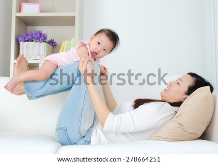 Asian mother lifting up her baby - stock photo